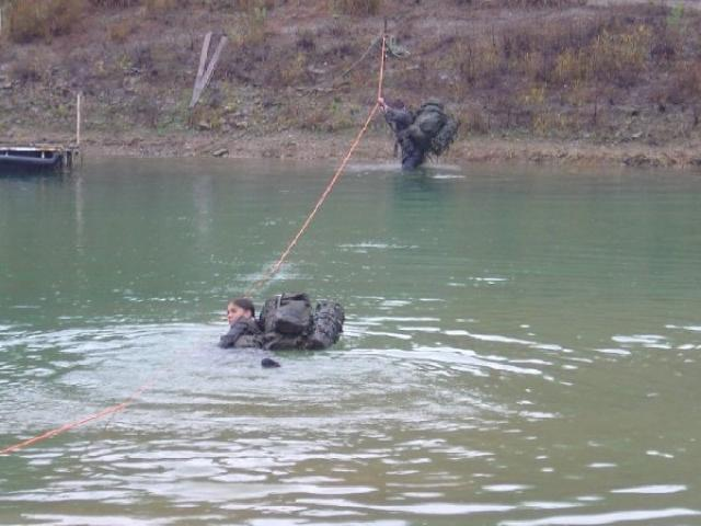 two troopers usiong a rope to cross the river whilst fully equiped