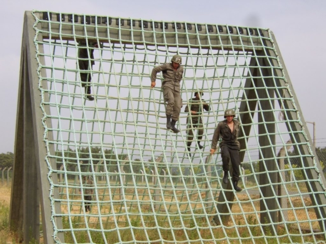 some men jumping through a structure using a rope net
